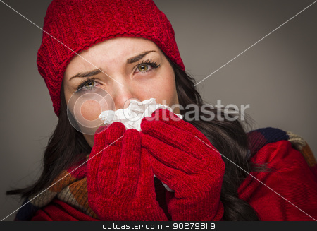 Sick Mixed Race Woman Blowing Her Sore Nose With Tissue stock photo, Sick Mixed Race Woman Wearing Winter Hat and Gloves Blowing Her Sore Nose with a Tissue. by Andy Dean