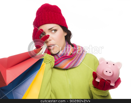Concerned Expressive Mixed Race Woman Holding Shopping Bags and  stock photo, Concerned Expressive Mixed Race Woman Wearing Winter Clothing Holding Shopping Bags and Piggybank Isolated on White Background. by Andy Dean