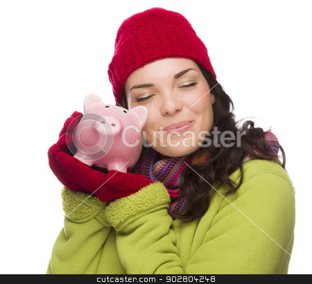 Pleased Mixed Race Woman Hugging Piggybank Isolated on White  stock photo, Pleased Mixed Race Woman Wearing Winter Clothing Hugging Piggybank Isolated on White Background. by Andy Dean
