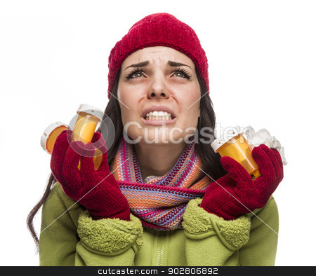 Sick Mixed Race Woman with Empty Medicine Bottles Blowing Nose  stock photo, Sick Mixed Race Woman Wearing Winter Hat and Gloves Blowing Her Sore Nose and Holding Empty Medicine Bottle Isolated on White.  by Andy Dean