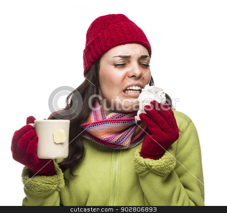 Sick Mixed Race Woman Drinks Hot Tea While Blowing Nose  stock photo, Sick Mixed Race Woman Wearing Winter Hat and Gloves Blowing Her Sore Nose and Holding Cup of Hot Tea Isolated on White.  by Andy Dean