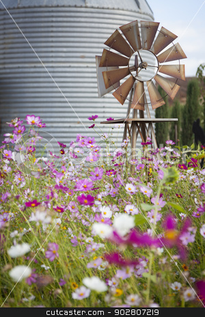 Antique Farm Windmill and Silo in a Flower Field  stock photo, Antique Farm Windmill and Silo near a Flower Field in a Beautiful Country Outdoor Setting.  by Andy Dean