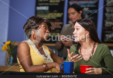 Diverse Friends Talking in Cafe stock photo, African and European women in a coffee house talking by Scott Griessel