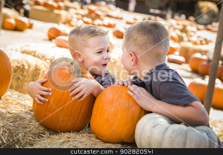 Two Boys at the Pumpkin Patch Talking and Having Fun stock photo, Two Boys at the Pumpkin Patch Talking About Their Pumpkins and Having Fun on a Fall Day.  by Andy Dean