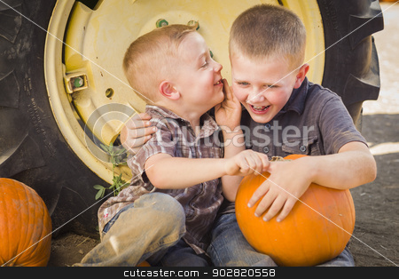 Two Boys Sitting Against Tractor Tire Holding Pumpkins Whisperin stock photo, Two Boys Sitting Against a Tractor Tire Holding Pumpkins and Whispering Secrets in Rustic Setting. by Andy Dean