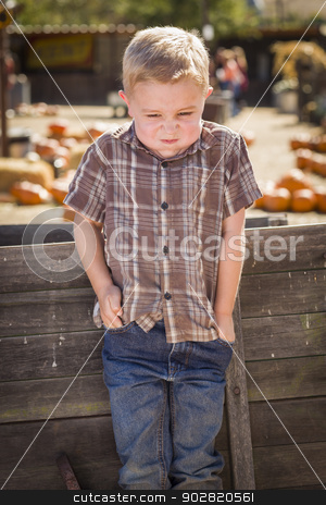 Frustrated Boy at Pumpkin Patch Farm Standing Against Wood Wagon stock photo, Frustrated Little Boy at Pumpkin Patch Farm Standing Against Old Wood Wagon.  by Andy Dean
