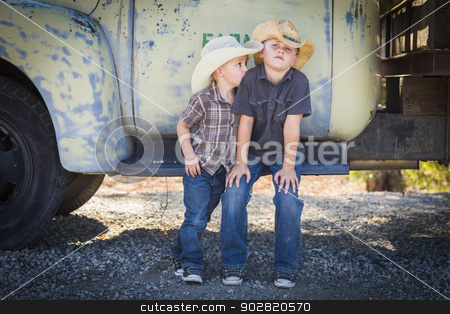 Two Young Boys Wearing Cowboy Hats Leaning Against Antique Truck stock photo, Two Young Boys Wearing Cowboy Hats Leaning Against an Antique Truck in a Rustic Country Setting.  by Andy Dean