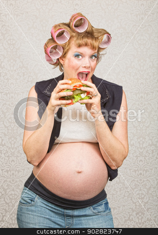 Pregnant Woman Eating a Sandwich stock photo, Happy female hillbilly in curlers eating a sandwich by Scott Griessel