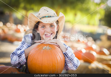 Preteen Girl Portrait at the Pumpkin Patch stock photo, Portrait of Preteen Girl Wearing Cowboy Hat Playing at the Pumpkin Patch in a Rustic Country Setting.  by Andy Dean