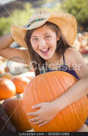 Preteen Girl Holding A Large Pumpkin at the Pumpkin Patch stock photo, Preteen Girl Holding A Large Pumpkin at the Pumpkin Patch in a Rustic Setting. by Andy Dean