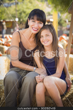 Attractive Mother and Daughter Portrait at the Pumpkin Patch stock photo, Attractive Mother and Baby Daughter Portrait in a Rustic Ranch Setting at the Pumpkin Patch.  by Andy Dean