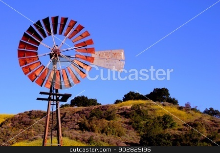 Water Pumping Windmill stock photo, Water pumping windmill with a hill and blue sky in the background. by Henrik Lehnerer