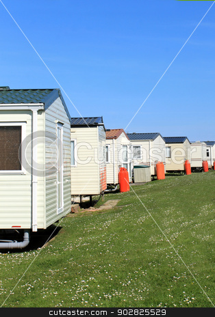 Row of caravans in trailer park stock photo, Scenic view of row of caravans in trailer park with blue sky background. by Martin Crowdy