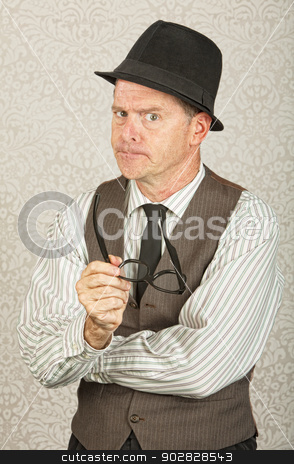 Strict Businessman stock photo, Single strict businessman in fedora holding eyeglasses by Scott Griessel