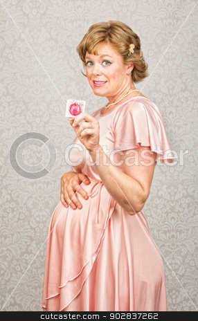 Embarrassed Woman with Condom stock photo, Embarrassed pregnant woman in dress holding contraceptives by Scott Griessel