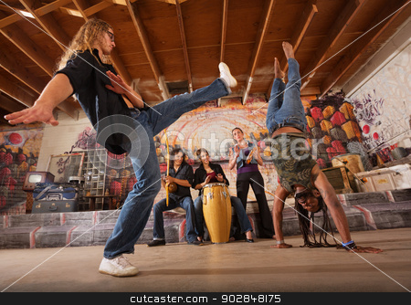 Capoeira Performers Kicking stock photo, Capoeira artist kicking towards man in handstand during performance by Scott Griessel