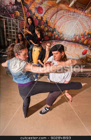 Capoeira Instructor Teaching Kicks stock photo, Capoeira instructor teaching woman how to do a roundhouse kick by Scott Griessel