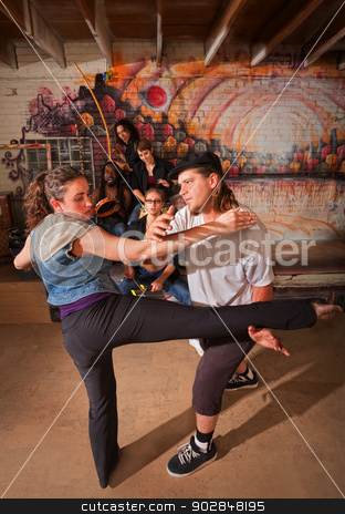 Capoeira Instructor Teaching a Woman stock photo, Young group of capoeira performers in urban building by Scott Griessel