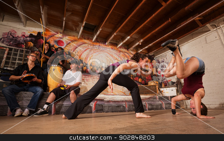 Capoeira Fighters and Musicians stock photo, Group of capoeira performers with music in urban building by Scott Griessel