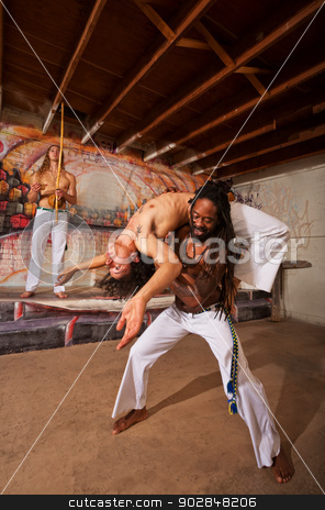 Capoeira Back Bending stock photo, Capoeira performer holding partner in back bending over shoulders by Scott Griessel