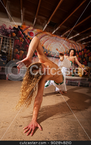 Male Capoeira Performers Fighting stock photo, Young pair of capoeira fighting in urban basement by Scott Griessel