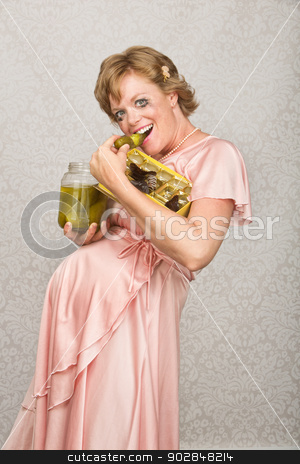Smiling Pregnant Woman Eating stock photo, Grinning pregnant lady eating candy and pickles by Scott Griessel