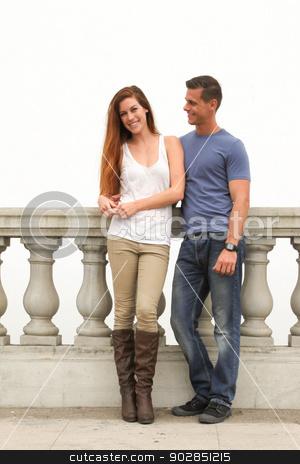 Young Couple Bridge stock photo, Young couple sitting on a bridge. by Henrik Lehnerer