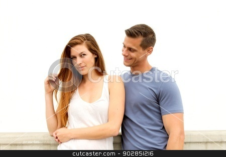 Young Couple stock photo, Young couple standing in front of a white wall. by Henrik Lehnerer