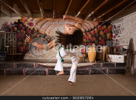 Capoeira Performer Leaping Up stock photo, Young capoeira expert flipping over indoors by Scott Griessel