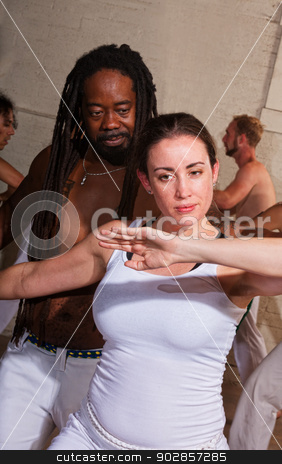 Capoeira Master with Student stock photo, Cheerful capoeira master working with female student indoors by Scott Griessel