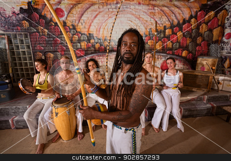 Capoeira Man with Dreadlocks and Instruments stock photo, Capoeira teacher with dreadlocks and students playing music  by Scott Griessel