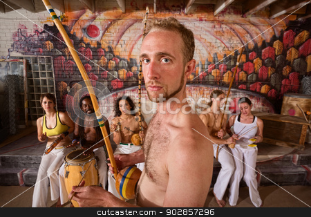Capoeira Performer Playing Music stock photo, Serious male capoeira performer with group playing music by Scott Griessel