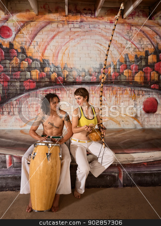 Capoeira Couple Playing Music stock photo, Cute mixed couple in capoeira clothing playing African music by Scott Griessel