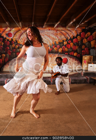 Drummer and Woman Dancing stock photo, Happy Brazillian dancer and pandeiro performing indoors by Scott Griessel