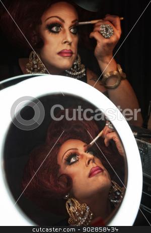 Man in Drag with Makeup stock photo, Cross dressing man putting on makeup at a mirror by Scott Griessel