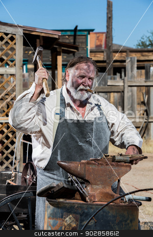 Old West Blacksmith stock photo, Male Blacksmith in Old West Swings Hammer at Anvil by Scott Griessel