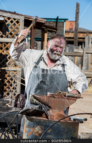Old West Blacksmith stock photo, Old West Blacksmith Swings Hammer at an Anvil by Scott Griessel