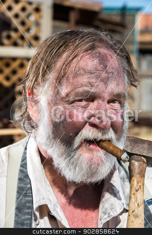 Old West Blacksmith stock photo, Old West Blacksmith Smokes Cigar While Holding Mallet by Scott Griessel