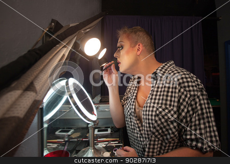 Man Using Lipstick Pencil stock photo, Serious male drag queen performer using lipstick pencil by Scott Griessel