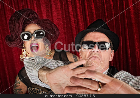 Surprised Famous People stock photo, Over-protective man in hat with surprised drag queen by Scott Griessel