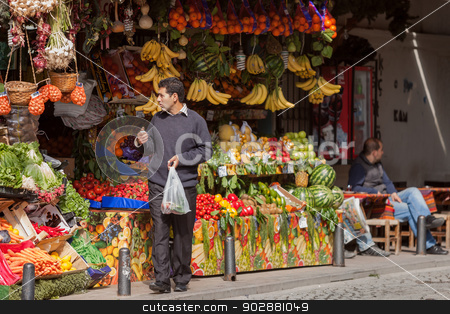 Fruit Stand in Istanbul stock photo, Istanbul, TURKEY – APRIL 28: Man leaves fruit stand with his purchase on April 28 2012 in Istanbul, Turkey.  Each year patriotic Turks honor those fallen at the battle of Galipoli during World War I. by Scott Griessel