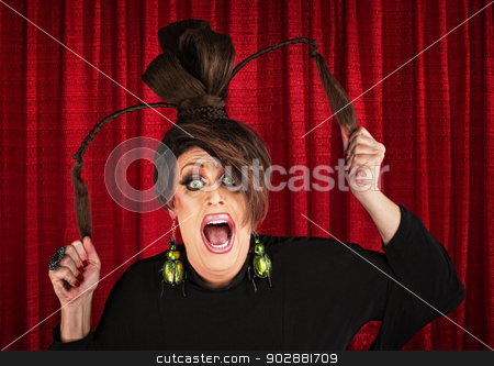 Screaming Drag Queen Pulling Hair stock photo, Desperate white drag queen over curtain pulling ponytails by Scott Griessel