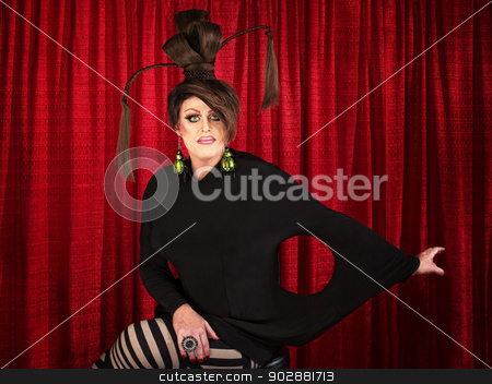 Unique Drag Queen Sitting stock photo, Grinning man in drag with unique dress and ponytails by Scott Griessel