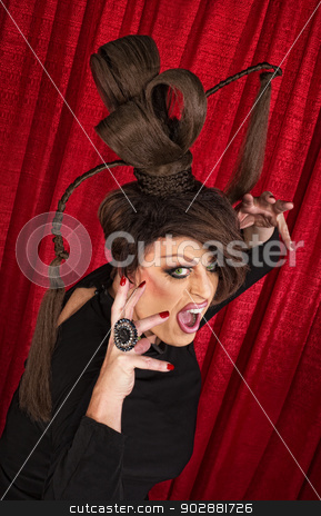 Fierce Drag Queen stock photo, Threatening drag queen in ponytail wig near curtain by Scott Griessel