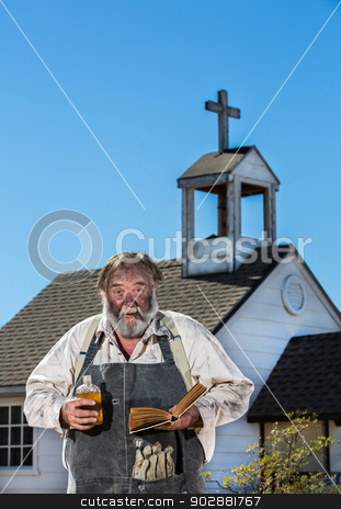 Old West Drunkard Holds Bible stock photo, Old West Drunkard Holds a Bible in front of Church by Scott Griessel