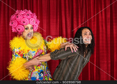 Drag Queen Pulling Man stock photo, Excited cross-dressing queen pulling on scared man by Scott Griessel