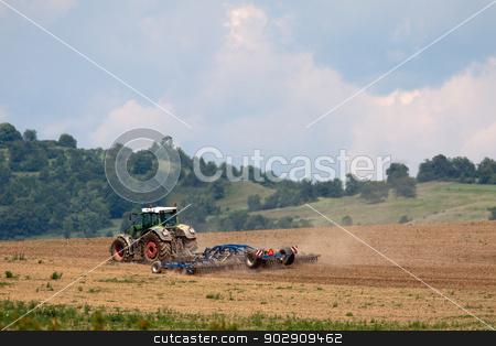 Tractor working on the field stock photo, Tractor plowing field with harrow, in the background sky and trees by Marian Bauer