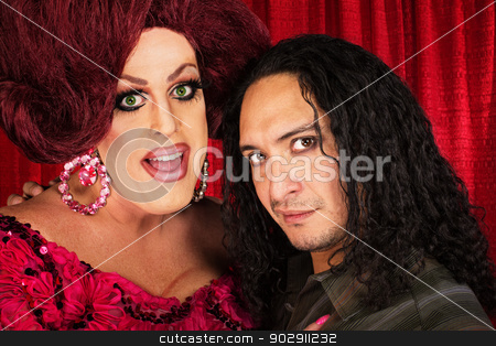 Transvestite with Male Partner stock photo, Big transvestite with sensual Hispanic man in front of curtain by Scott Griessel