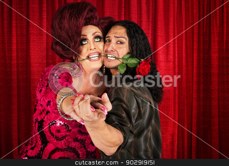 Embarrassed Man Dancing with Transvestite stock photo, Embarrassed man with rose in mouth dancing with drag queen  by Scott Griessel