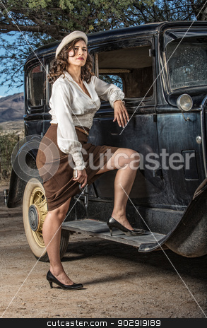 Beautiful Gangster Pin-Up stock photo, Beautiful armed gangster woman with leg up on car by Scott Griessel